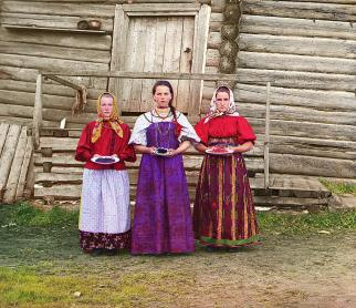 """Three young women offer berries to visitors to their izba, a traditional wooden house, in a rural area along the Sheksna River, near the town of Kirillov."" (Library of Congress)"