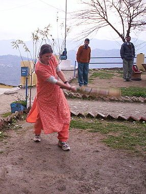 Woman playing cricket in a salwar kameez. Edited. Authors Meg and Rahul (Ranveig on Flickr). From Wikimedia Commons (CC BY 2.0)