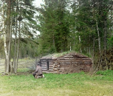 Hut in the forest, for woodcutters and kuria (coal burning). Small log cabin next to woods with man seated on log nearby. 1912. Sergei Prokudin-Gorskii / Public domain